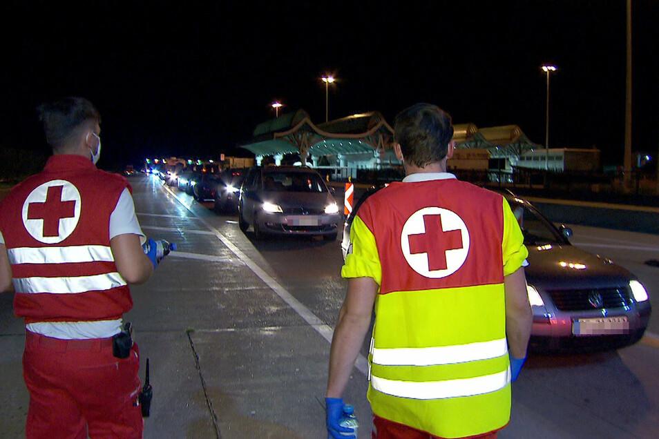 Mitarbeiter des Roten Kreuzes betreuen in der Nacht Autofahrer in einem kilometerlangen Stau bei der Einreise nach Österreich am Karawankentunnel.
