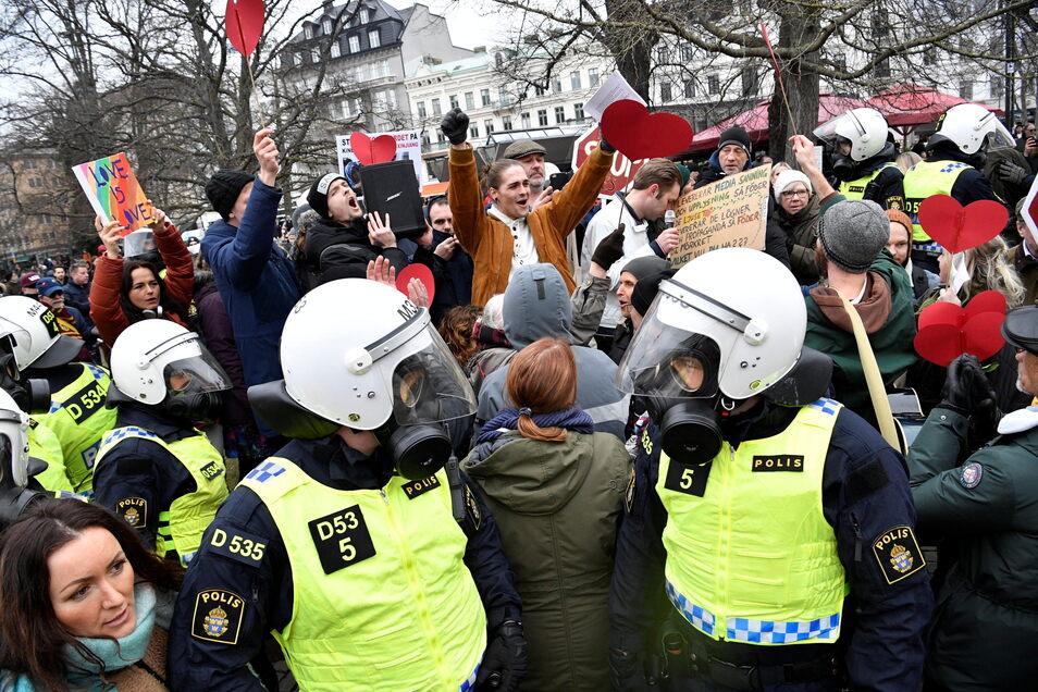 Bereitschaftspolizisten stehen in Malmö auf einer Straße bei einer Demonstration gegen die Maßnahmen zur Eindämmung des Coronavirus.