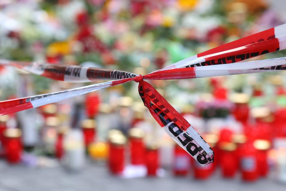 Würzburg: Blumen und Kerzen vor einem abgesperrten Kaufhaus, in dem ein Mann Menschen mit einem Messer attackiert hatte. Bei dem Angriff am 25.06.2021 hatte ein Somalier drei Frauen in einem Kaufhaus getötet.