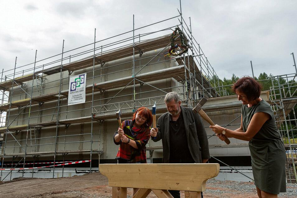 Oberbürgermeisterin Kerstin Körner (v.l.), SG Stahl-Vorsitzender Andreas Mannschatz und Schulleiterin Katrin Jungnickel schlagen symbolisch einen Nagel ein für die neue Turnhalle in Schmiedeberg.