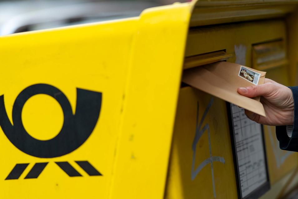 Ein Mann wirft einen Brief in einen Briefkasten. Demnächst werden die Portopreise steigen.
