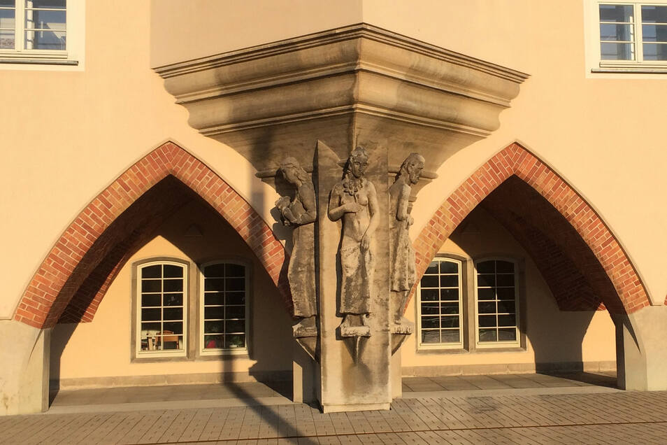 Der Treppenturm läuft unten in einer eleganten Risalitsäule aus, die drei überlebensgroße Figuren zieren und Arbeit, Jugend und Alter darstellen. Zu beiden Seiten des Risalits entstand ein Arkadengang mit Bögen in Schwalbenschwanzoptik.