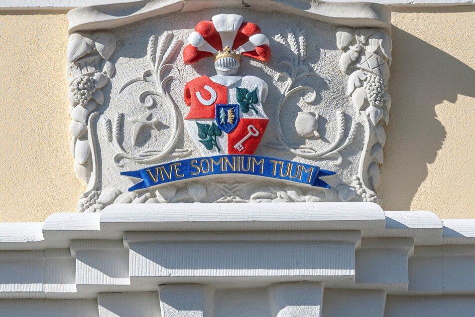 """Unter dem Wappen an der restaurierten Fassade des östlichen Torhauses steht der lateinische Spruch """"Vive somnium tuum"""". Übersetzt heißt er: """"Lebe Deinen Traum."""""""