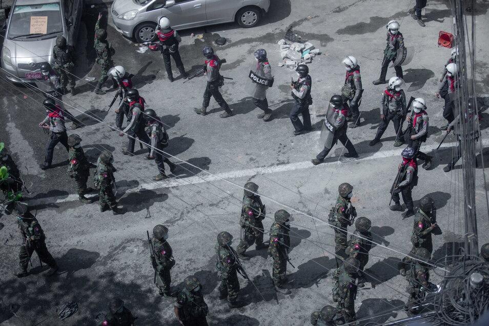 Myanmar, Rangun: Soldaten und Bereitschaftspolizisten gehen bei einem Protest gegen den Militärputsch auf einer Straße.