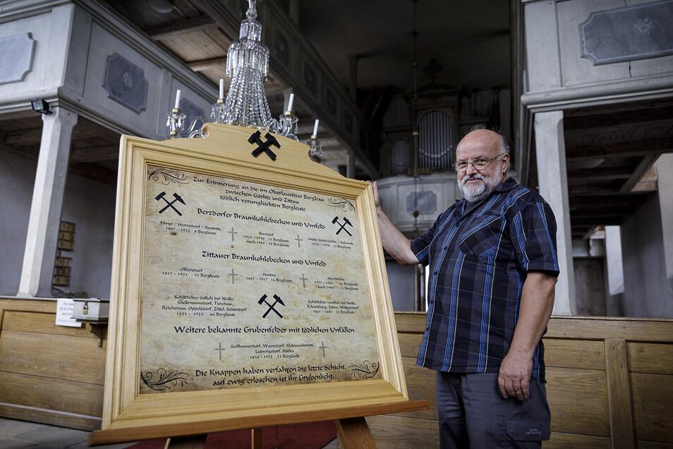 Joachim Neumann steht vor der Gedenktafel für tödlich verunglückte Bergleute, ausgestellt in der evangelischen Kirche in Tauchritz.