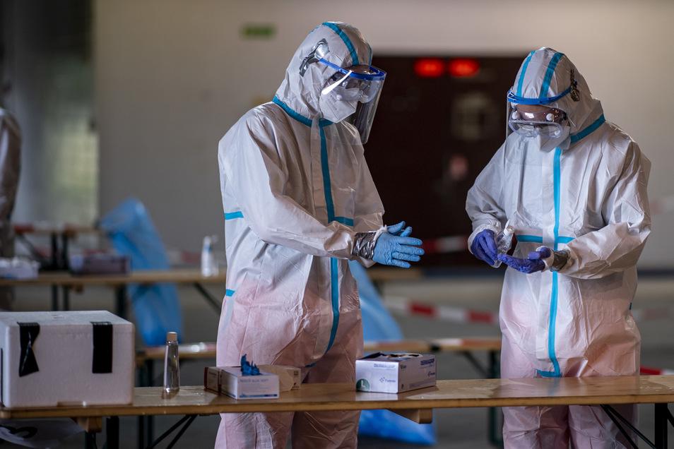 Schutzanzüge - wie hier auf dem Gelände des ehemaligen Militärflughafens Gütersloh - schützen vor dem Virus auf jeden Fall. Ob seine Mutationen tatsächlich gefährlicher werden, ist nicht klar.