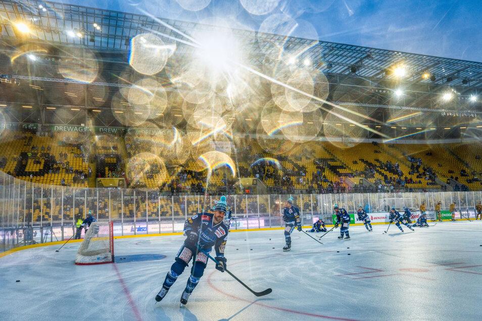 Die Pudelmütze schützt beim Aufwärmen im noch fast leeren Stadion vor dem Regen, der sich auf dem Kameraobjektiv spiegelt. Das Spiel der Dresdner Eislöwen gegen die Lausitzer Füchse wird zu einer wahren Wasserschlacht auf Eis.