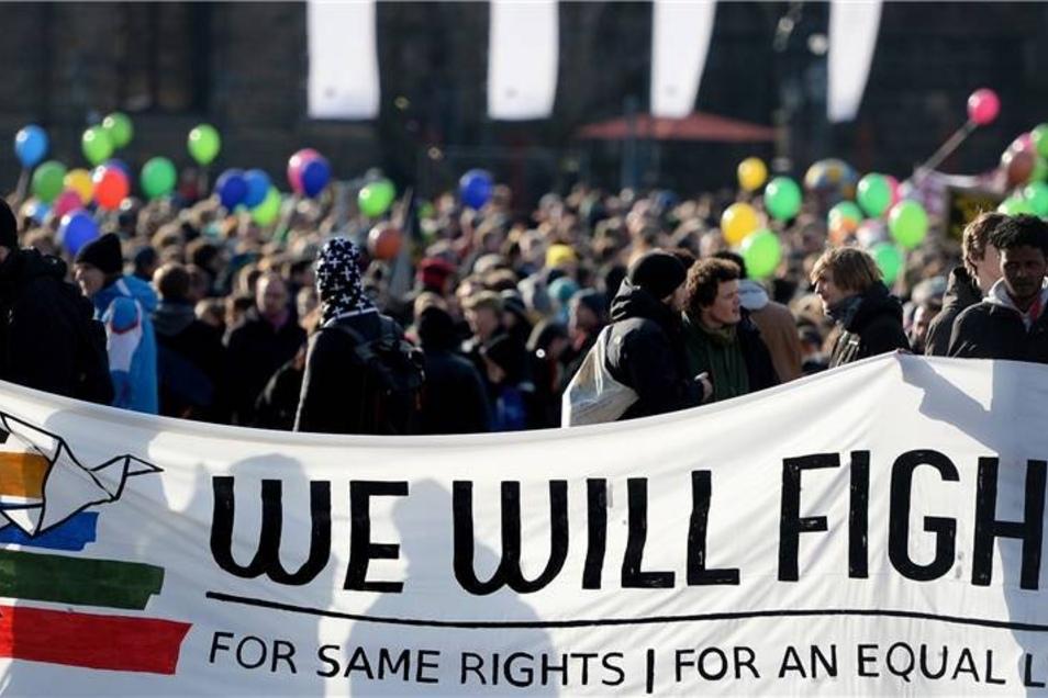 """Teilnehmer tragen ein Transparent mit dem Spruch """"Wir werden für gleiche Rechte für ein gleiches Leben kämpfen"""" auf dem Theaterplatz."""