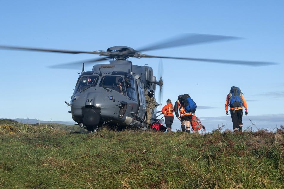 Neuseeland, Kahurangi National Park: Rettungshelfer gehen während eines Einsatzes an Bord eines Hubschraubers.