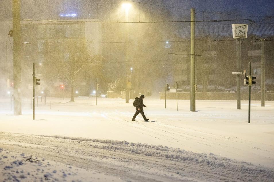 Nordrhein-Westfalen, Bielefeld: Ein Mann geht über eine zugeschneite Straße.