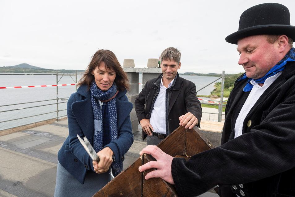 """Ina Lachmann und Henry Hedrich (Mitte) gemeinsam mit Martin Glaeser von der G.M.V. Dachbau GmbH bei der Grundsteinlegung für das """"Hotel der Sinne"""" am Berzdofer See."""