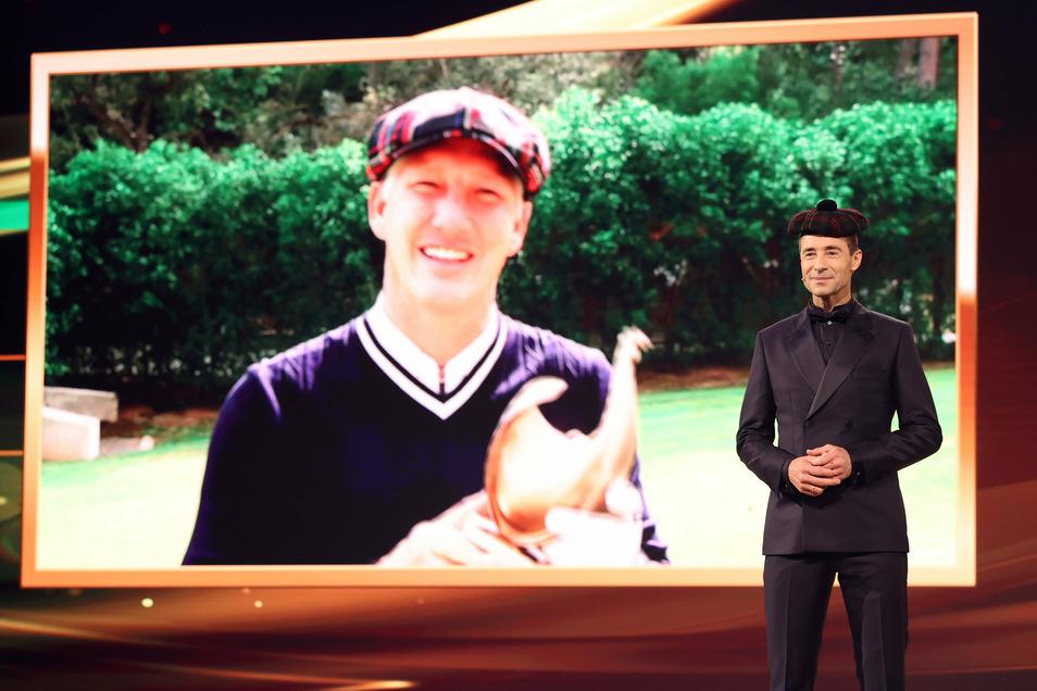 Der ehemalige Fußballspieler Basti Schweinsteiger ist bei einem Videoeinspieler zu sehen. Schweinsteiger erhält eine Goldene Henne. Im Vordergrund steht Moderator Kai Pflaume.