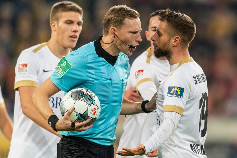Nach seiner Entscheidung, die Wiesbadener Führung beim Gastspiel in Dresden nicht anzuerkennen, muss Schiedsrichter Martin Petersen mit aufgebrachten Hessen diskutieren.