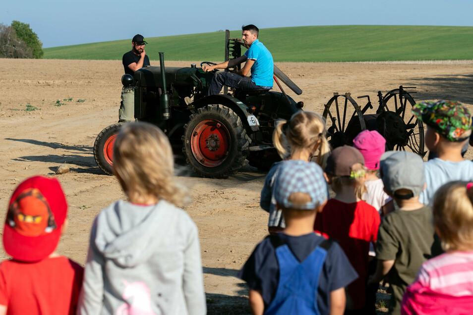 Die Kinder schauen zu, wie Marco Kretschmar mit seinem Traktor und einer Kartoffelschleuder die Kartoffeln aus der Erde holt.