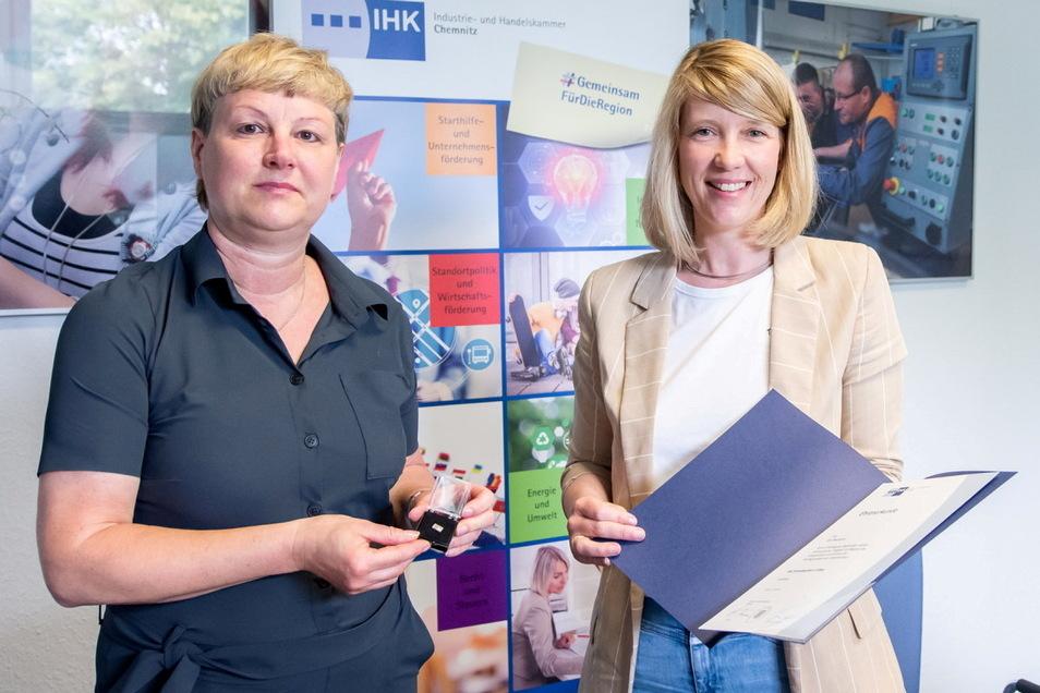 Aus den Händen von IHK-Geschäftsführerin Cindy Krause (rechts) erhält die Chefin des Döbelner Stadtwerberings, Grit Neumann, das IHK-Ehrenabzeichen in Silber.