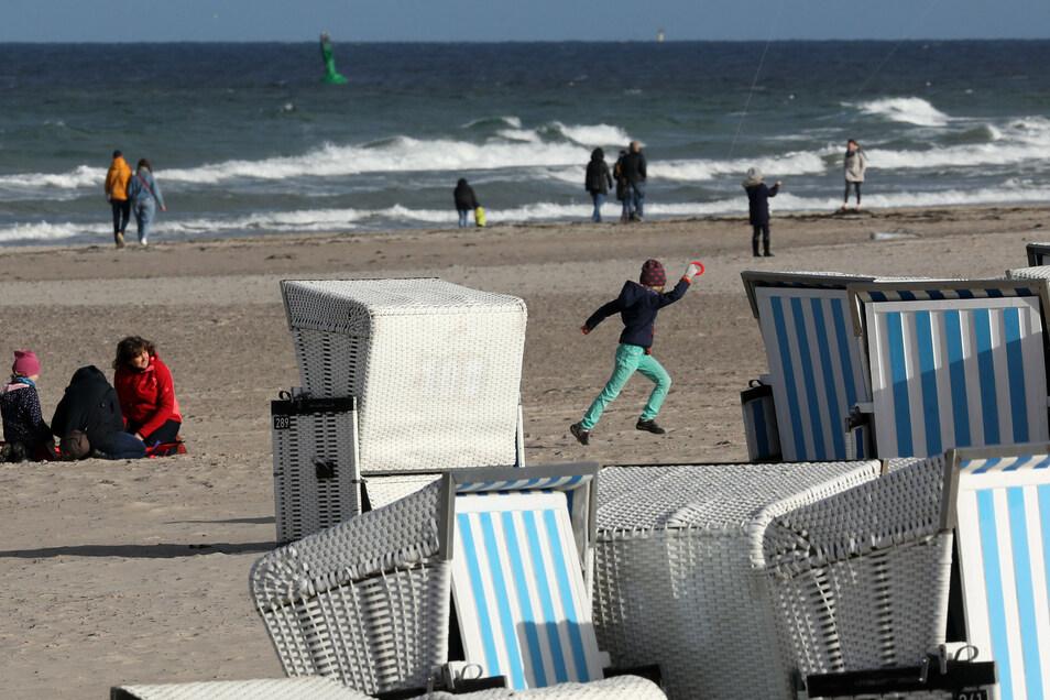 Am Ostseestrand von Warnemünde  sind Strandbesucher spazieren und lassen Drachen steigen.