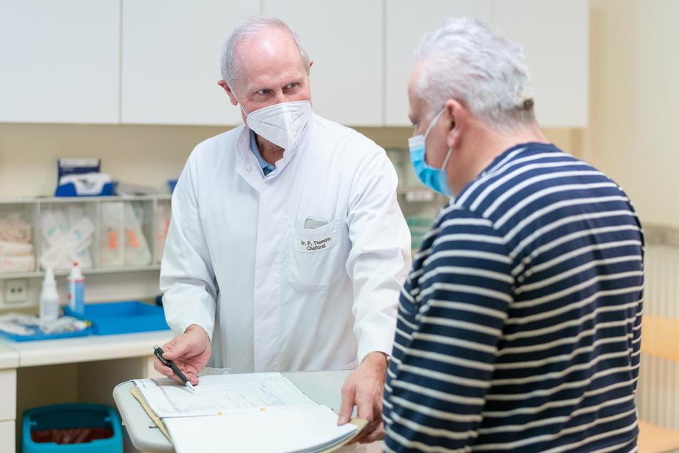 Chefarzt Dr. Themann im Gespräch mit einem Patienten.