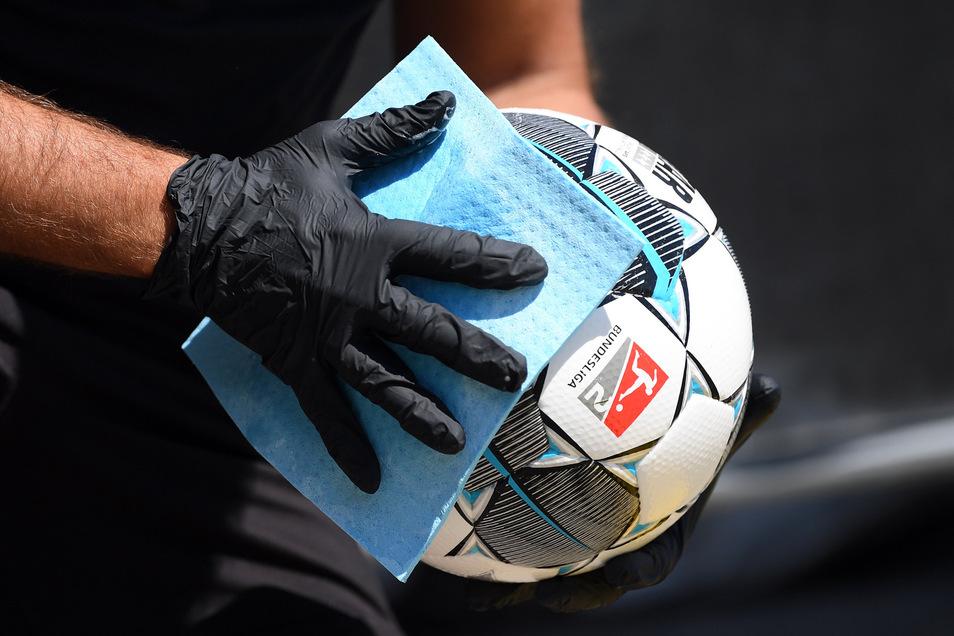 Bundesligafußball mit Besonderheiten. In regelmäßigen Abständen werden die Bälle desinfiziert. Viele Sportler der Region haben allerdings überhaupt kein Verständnis, dass die Profis spielen dürfen.