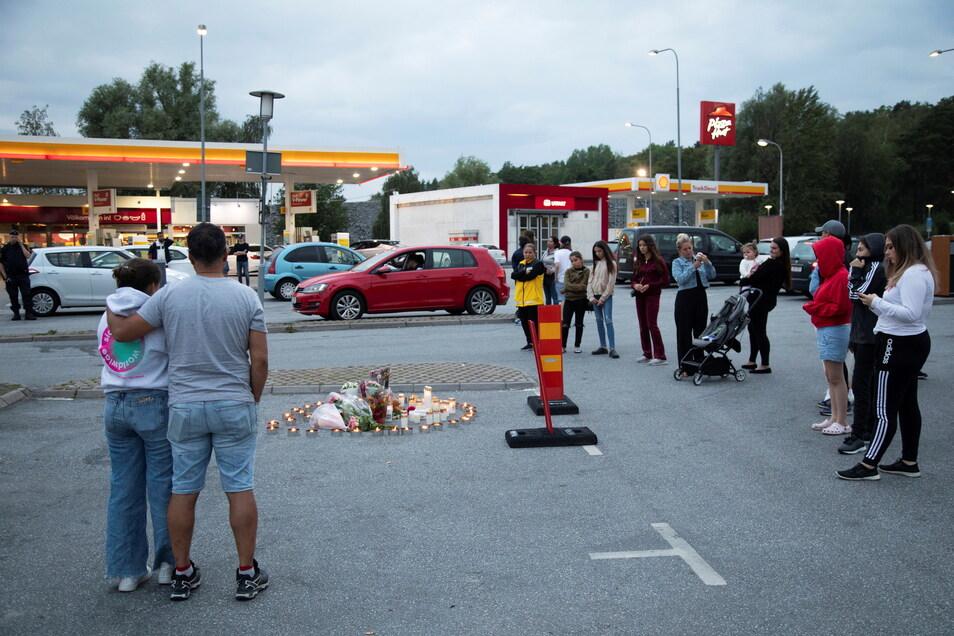 Menschen stehen neben Blumen und Kerzen nahe einer Tankstelle in Botkyrka. Ein zwölfjähriges Mädchen dort Anfang August 2020 angeschossen worden und später ihren Verletzungen erlegen.