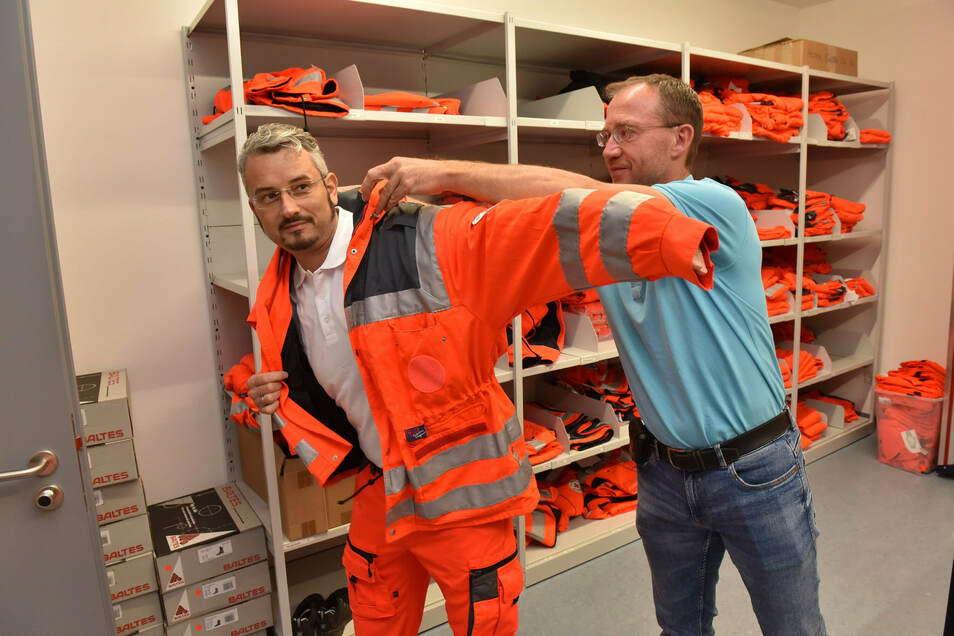 Der Praktikant wird eingekleidet: Rettungswachenleiter Jan Göbel verpasst Reporter Jörg Stock die orange Einsatzkluft der Sanitäter.
