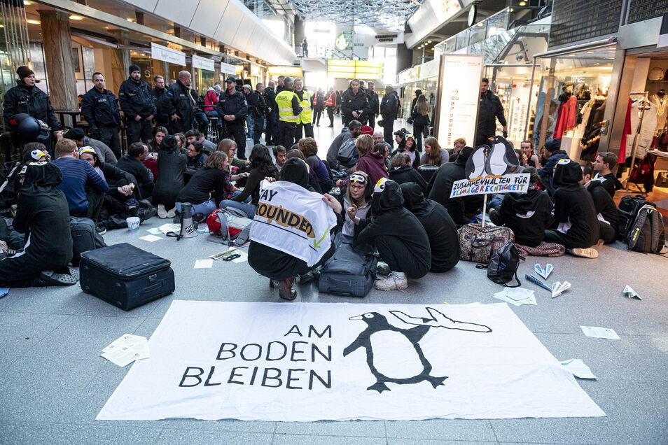 """Demonstranten des Bündnisses """"Am Boden bleiben"""" blockieren die Haupthalle des Flughafen Tegels."""