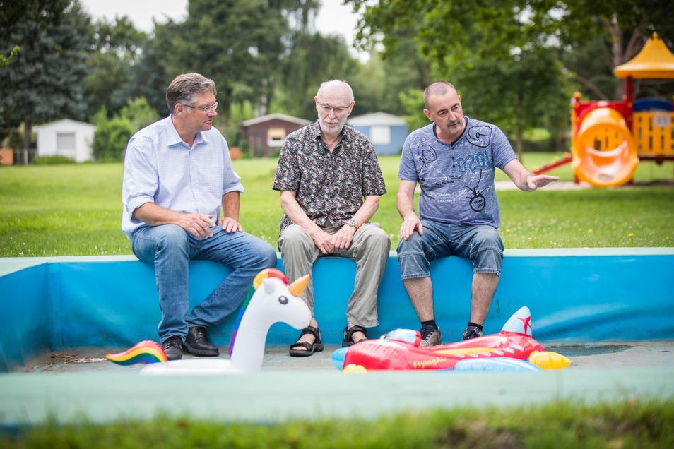 Holger Zastrow (l.) sieht sich mit Siedler Uwe Danusch (r.) und Steffen Nitzsche, dem Vater einer Siedlerin, das kaputte Kinderbecken an.