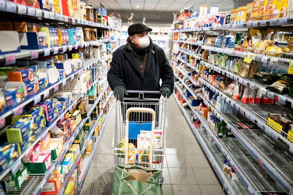 Ein Kunde kauft mit Mundschutz und Handschuhen  in einem Supermarkt ein.