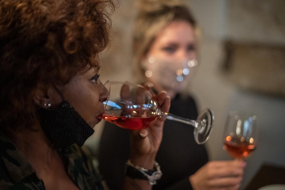 Sachsens Winzer leiden unter Umsatzausfällen durch die Corona-Auflagen. Langsam bessert sich die Lage: Ein weiblicher Gast trinkt in einer Dresdner Bar aus einem Glas Wein.