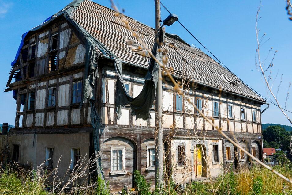 Die Planen, die das Umgebindehaus in der Bergstraße in Großschönau wegen des abgedeckten Daches schützen sollten, hängen zerfetzt herum. Eine Plane hat der Wind um die Straßenleuchte vor dem Gebäude gewickelt.