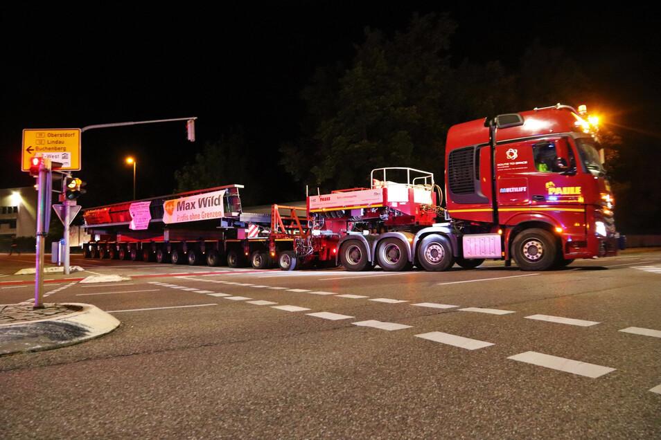 Ein Schwertransporter mit einem Stahlbauteil für eine neue Brücke ist in der Nacht unterwegs.