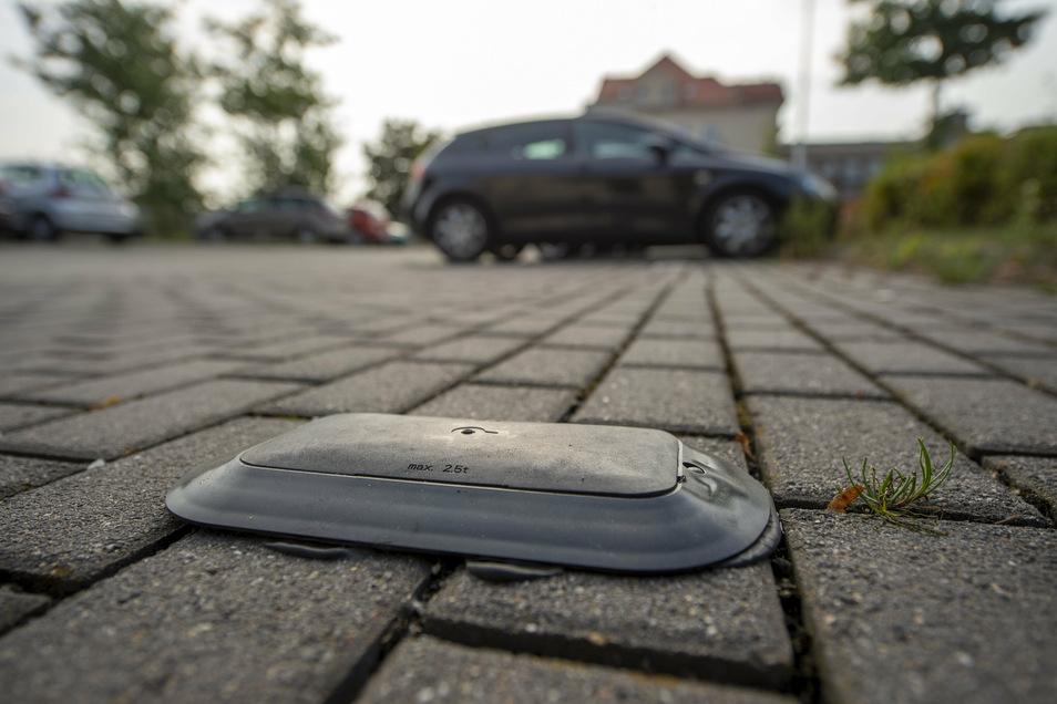 Der batteriebetriebene Sensor liegt fast unscheinbar relativ mittig auf einer Parkfläche auf der Park+Ride-Anlage an der Mittelstraße südlich des Bahnhofs Radebeul-Ost. Er überträgt an den VVO, ob der Stellplatz frei oder durch ein Auto belegt ist.