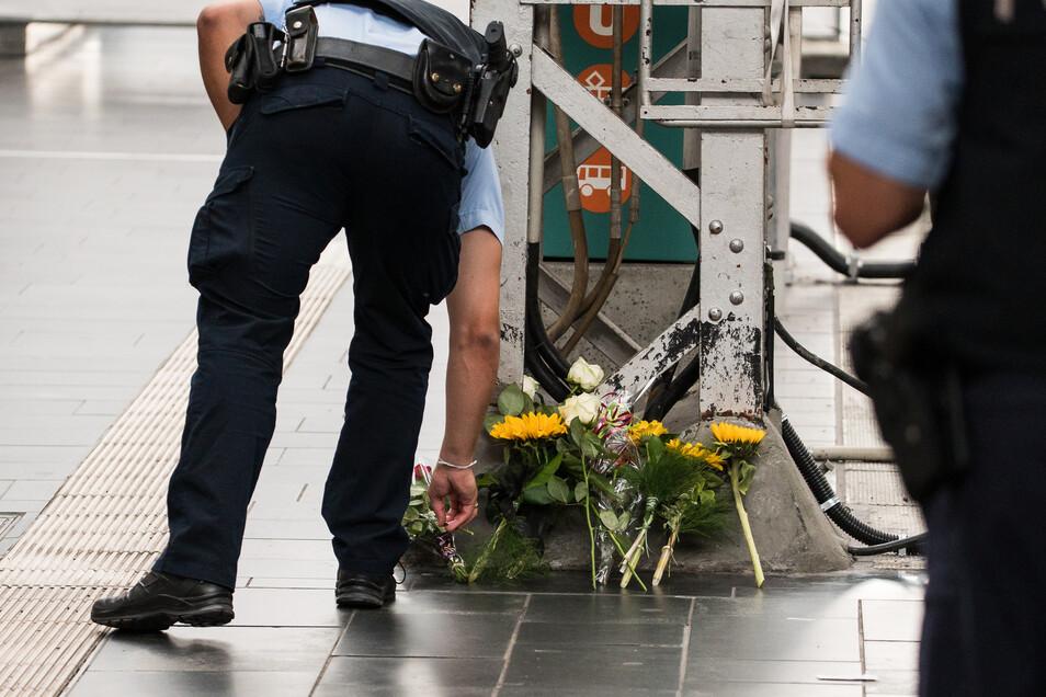 Ein Polizist legt im Frankfurter Hauptbahnhof Blumen für den getöteten Jungen nieder.