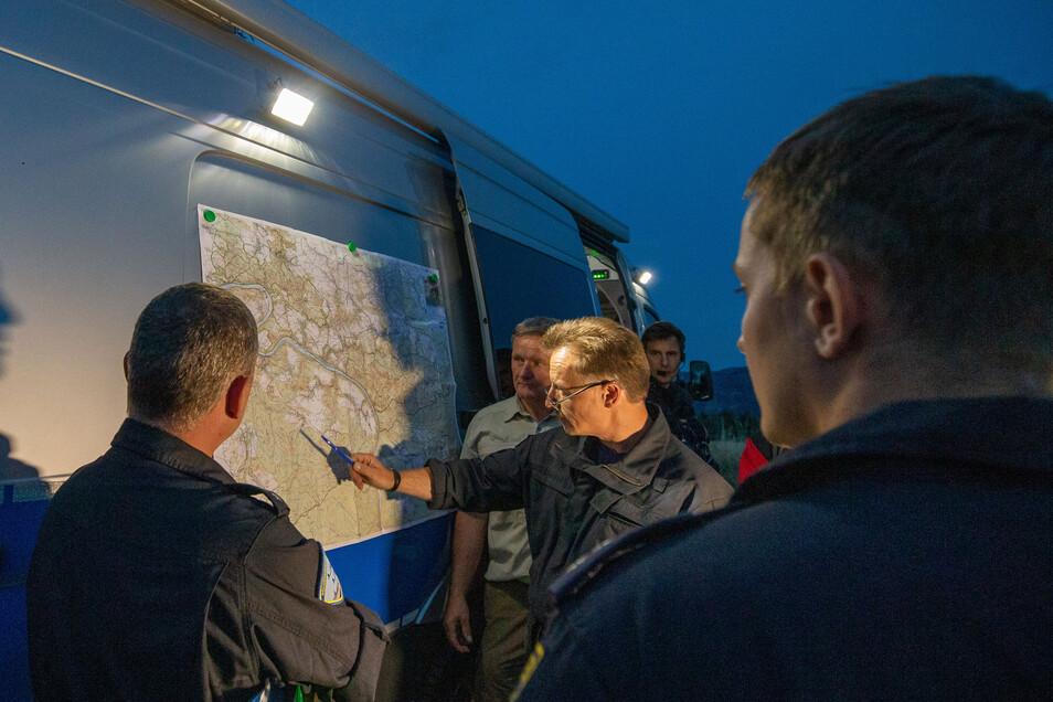 Polizeihauptkommissar Iven Eissner (Mitte) und Jens Posthoff (2.v.l.) vom Nationalpark besprechen mit der Hubschrauberbesatzung das Einsatzgebiet.