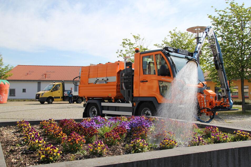 Ohne den Multicar zu verlassen, steuert der Fahrer den Gießarm bei der Bewässerung des Hochbeetes im Stadtzentrum.