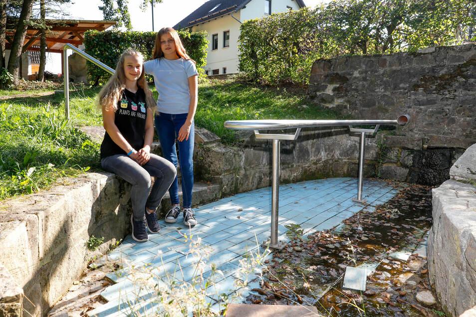Emely (links) und Virgenie aus Lückendorf im ausgetrockneten Wassertretbecken. Die beiden haben den Oybiner Gemeinderäten gezeigt, wie man das anpackt.