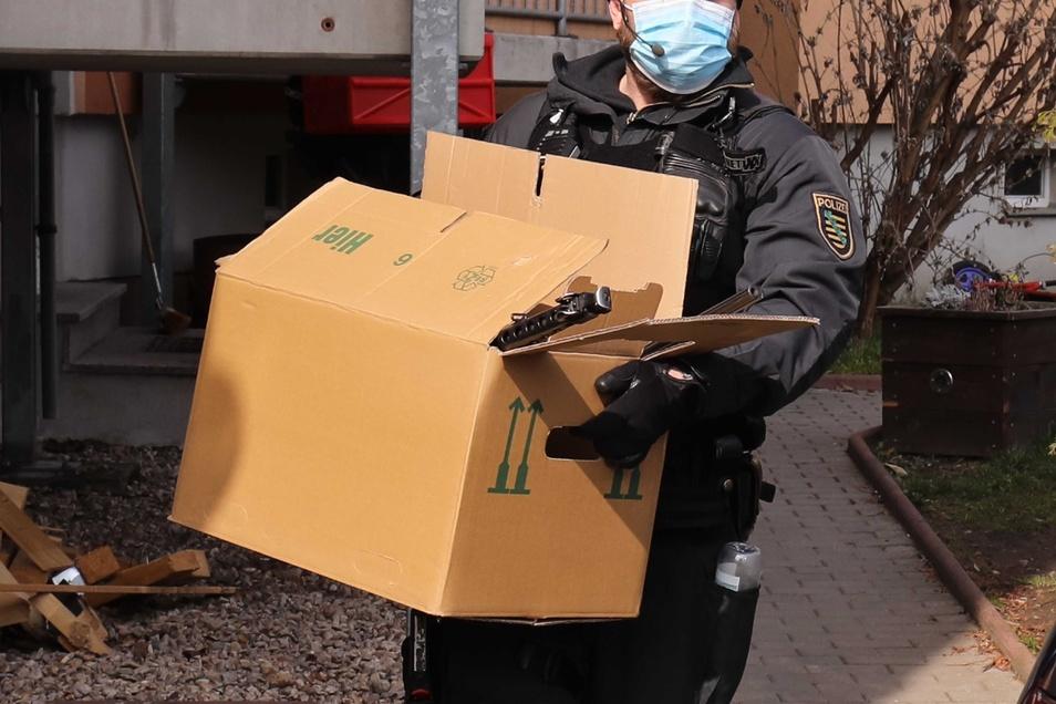 Das LKA holt Gegenstände mit Kisten aus einer Wohnung nur wenige Straßen weiter.