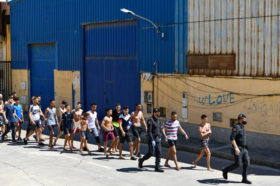 Eine Gruppe junger Migranten wird in der spanischen Nordafrika-Exklave Ceuta von Polizisten eskortiert.