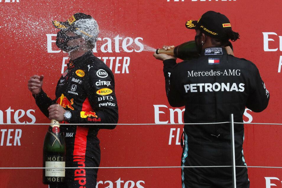 Champagner-Dusche mit Maske: Max Verstappen (l.) feiert seinen überraschenden Erfolg beim Rennen in Silverstone. Dem WM-Dominator Lewis Hamilton bleibt diesmal nur der zweite Platz.