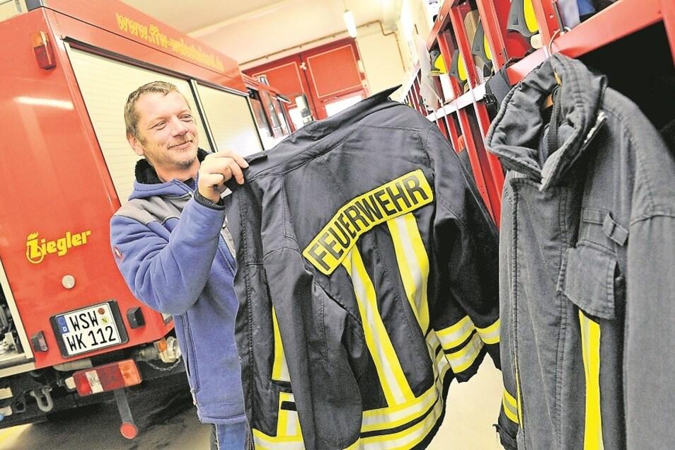 Ausgedient hat die Schutzkleidung der Feuerwehr in Weißkeißel, wie Ronny Scholz zeigt. Neue Uniformen sind bereits bestellt.