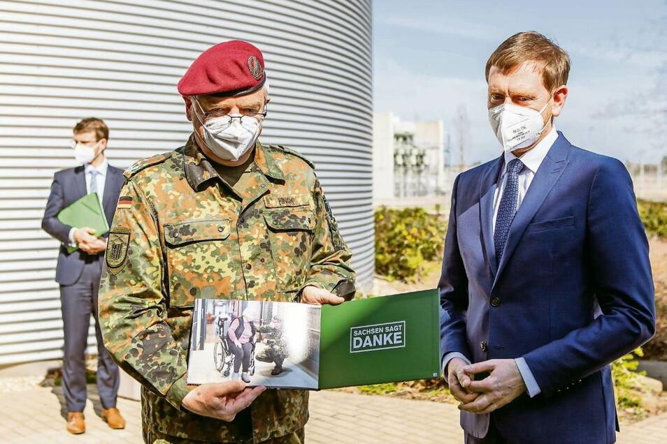 Die emotionalsten Momente des Corona-Einsatzes der Bundeswehr 2020 in Sachsen sind in einem Buch festgehalten. Oberst Klaus Finck, Kommandeur des Landeskommandos Sachsen, und Ministerpräsident von Sachsen Michael Kretschmer sind sich einig, dass die Bund