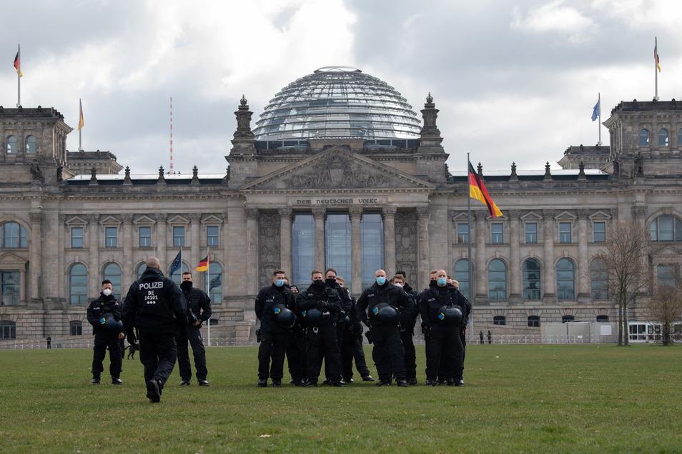 Polizeibeamte stehen vor dem Deutschen Bundestag und beobachten Demonstranten, die gegen die Verschärfung des Infektionsschutzgesetzes protestierten.