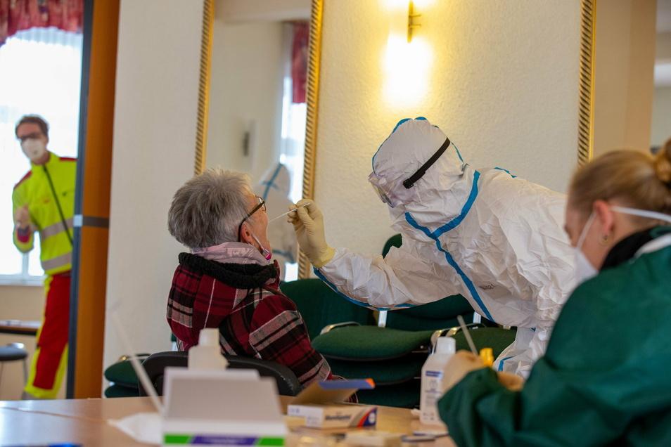 Einer älteren Dame wird in Rathmannsdorf eine Rachenprobe entnommen. Laut Robert Koch-Institut gibt es im Landkreis Sächsische Schweiz-Osterzgebirge eine 7-Tage-Inzidenz von 470 .