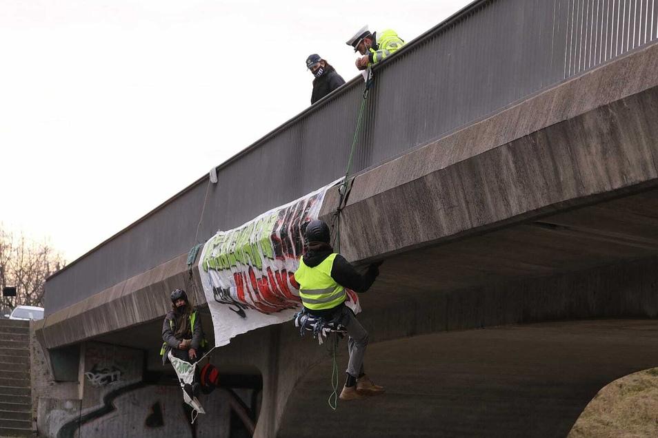 Zwei Protestierer haben sich an Seilen an die Brücke gehängt.