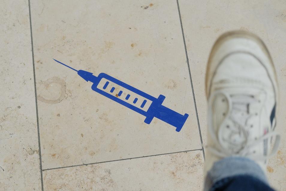 Das Symbol einer Spritze ist auf dem Boden der Muldentalhalle in Grimma aufgeklebt. Dort wird ein Impfzentrum betrieben.