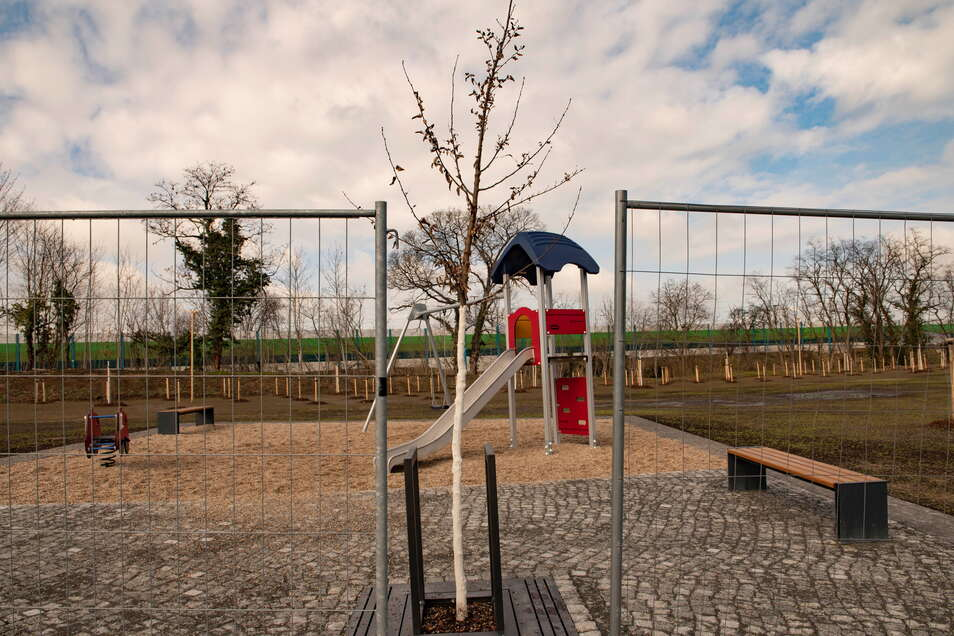 Bauzäune schützen noch immer den neuen kleinen Park in Zschieschen mit seinen Pflanzungen und Spielgeräten.