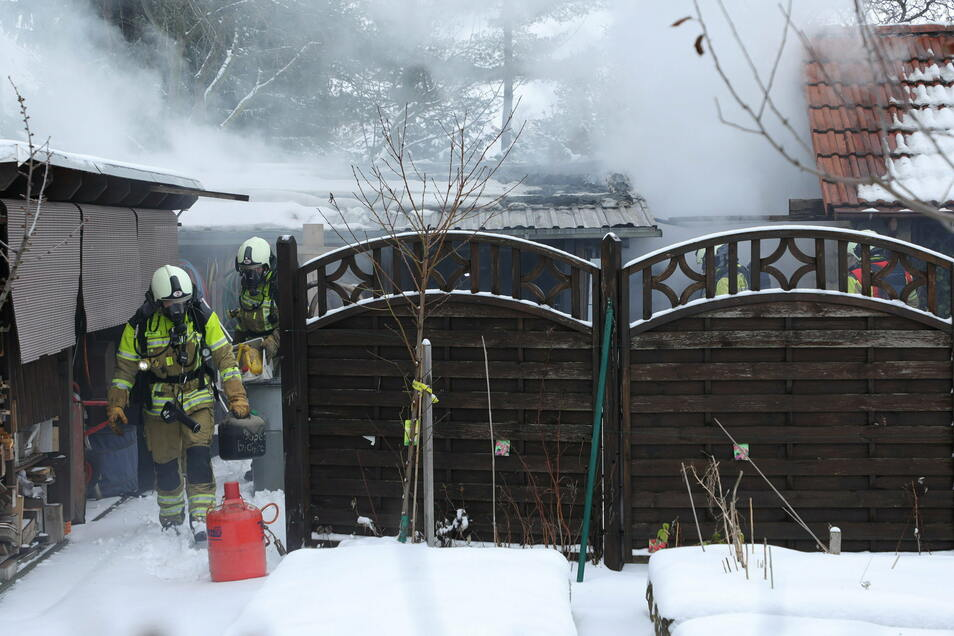 Während der Löscharbeiten bringt die Dresdner Feuerwehr auch zwei Propangasflaschen und einen Benzinkanister in Sicherheit.