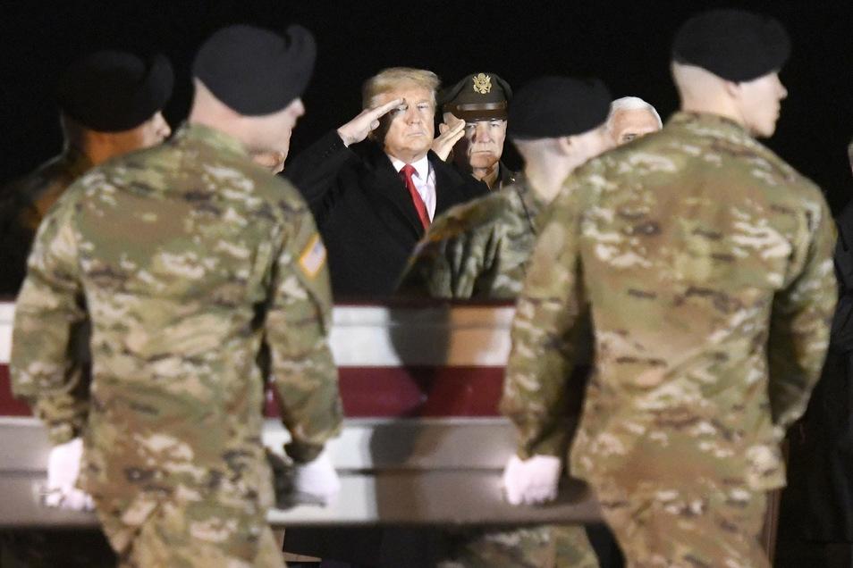 Donald Trump (M) salutiert vor dem Sarg eines gefallenen US-Soldaten. Inmitten brisanter Enthüllungen über angebliches russisches Kopfgeld auf US-Soldaten in Afghanistan ist ein Streit darum entbrannt, wie viel US-Präsident davon wusste.