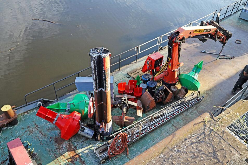 Im Riesaer Hafen ist ein Blick von oben auf den Arbeitsprahm möglich: er zeigt Kran, Ersatztonnen und einen stählernen Pfahl, mit dem der Verband am Grund festgelegt werden kann.