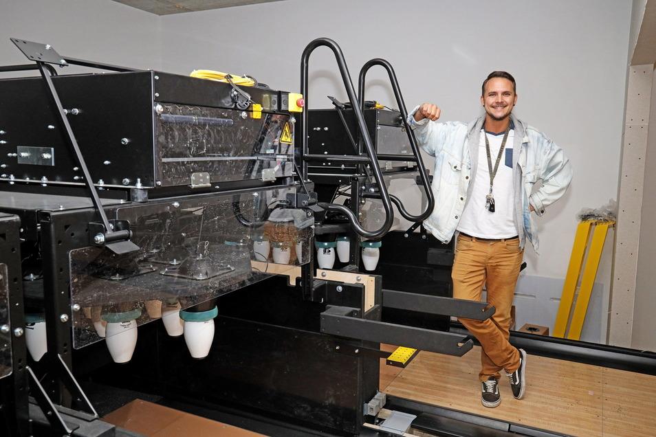 Marcel Voss steht vor den Pinsettern. Insgesamt vier Automaten stellen die Kegel auf.