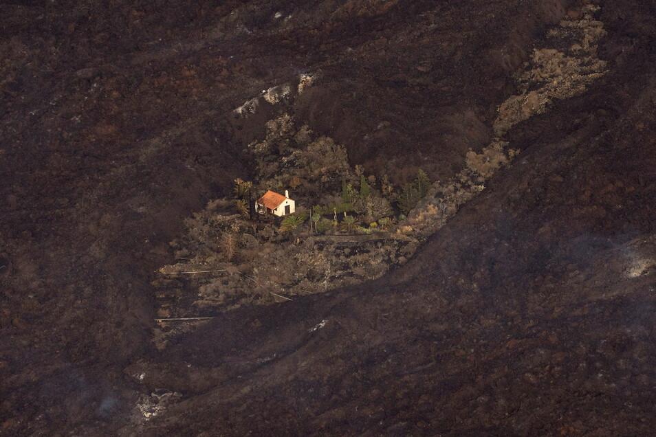 Lava von einem Vulkanausbruch umgibt ein Haus auf der Insel La Palma.